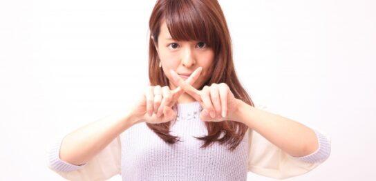 指でバツ印をつくる女性1